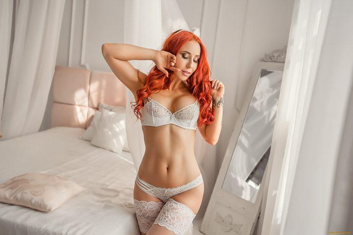 Сексуальная девушка с огненными рыжими волосами в нежном белом белье.