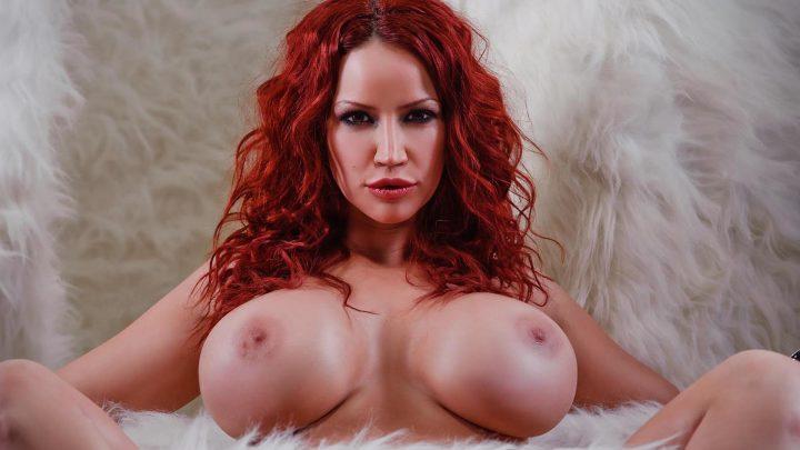 Кудрявая рыжая девушка с большими сиськами сидит в пушистом пледе.