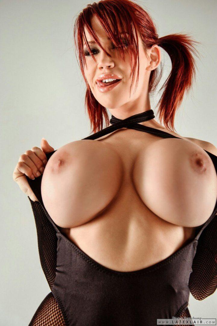 Развратная женщина с рыжими хвостами и с огромными силиконовыми сиськами.