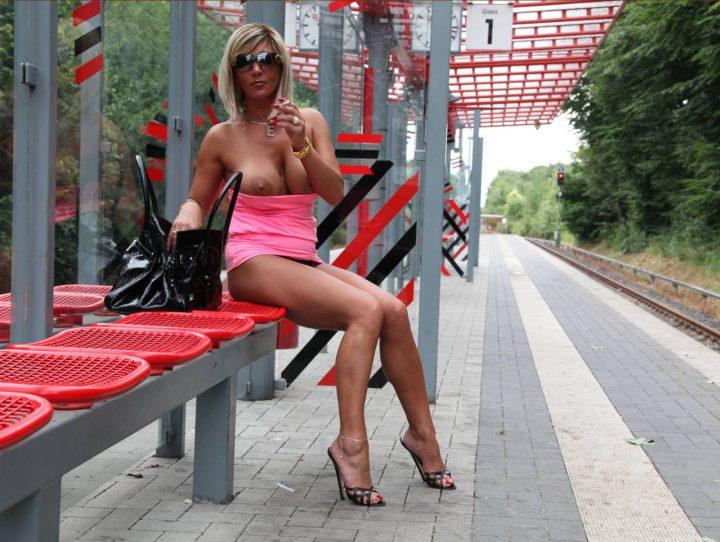 Раскрепощенная женщина сидит на вокзале с голыми сиськами и курит