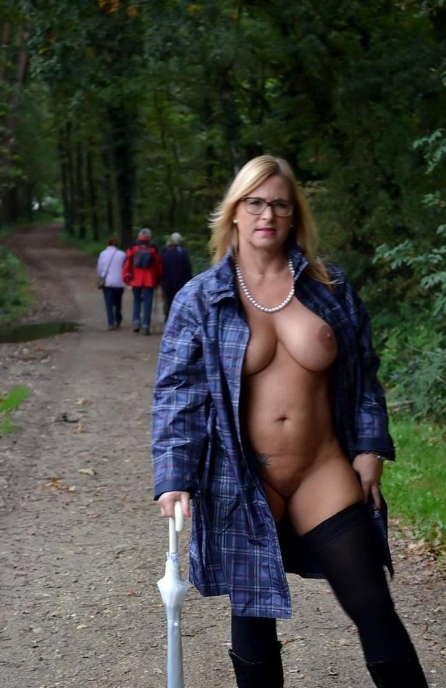 Красивая милфа в очках прогуливается по лесу голой в рубашке и с зонтом