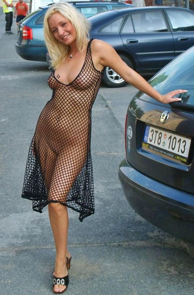 Соблазнительная женщина в прозрачном платье на голое тело ходит по улице