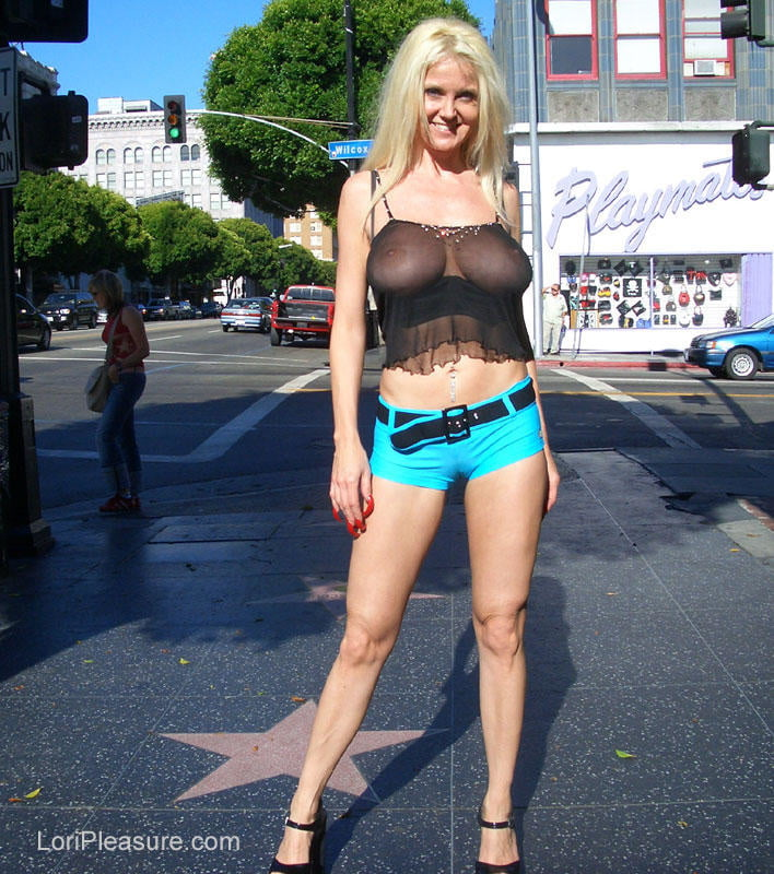 Красивая блондинка на улице не ходит в лифчике и показывает свои сиськи