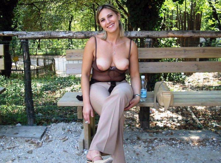Симпатичная женщина сидит на лавочке и курит с голыми сиськами