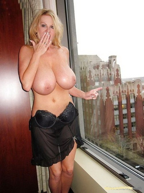 Блондинка в возрасте стоит у большого окна с голыми сиськами
