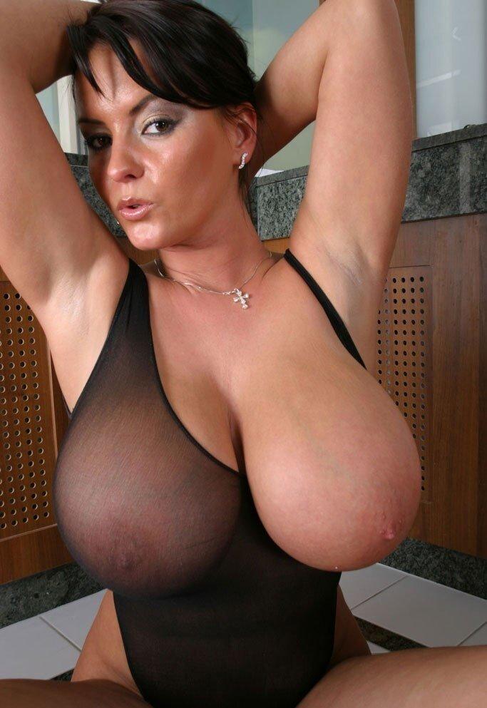 Раскованная женщина в прозрачном боди и с огромными буферами