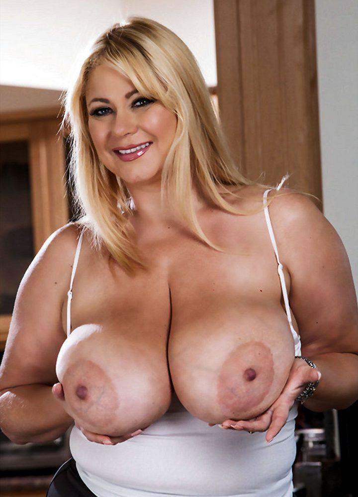 Шикарная блондинка в своих руках держит огромные сиськи
