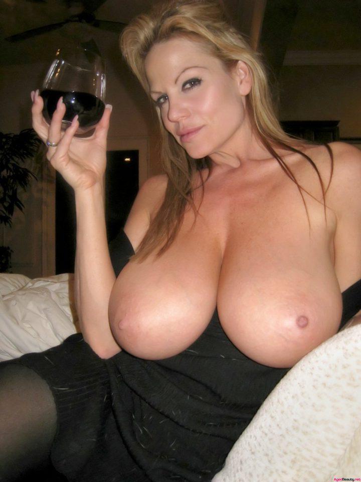 Блондинка с черными глазами и с большими сиськами с бокалом в руках сидит на кровати