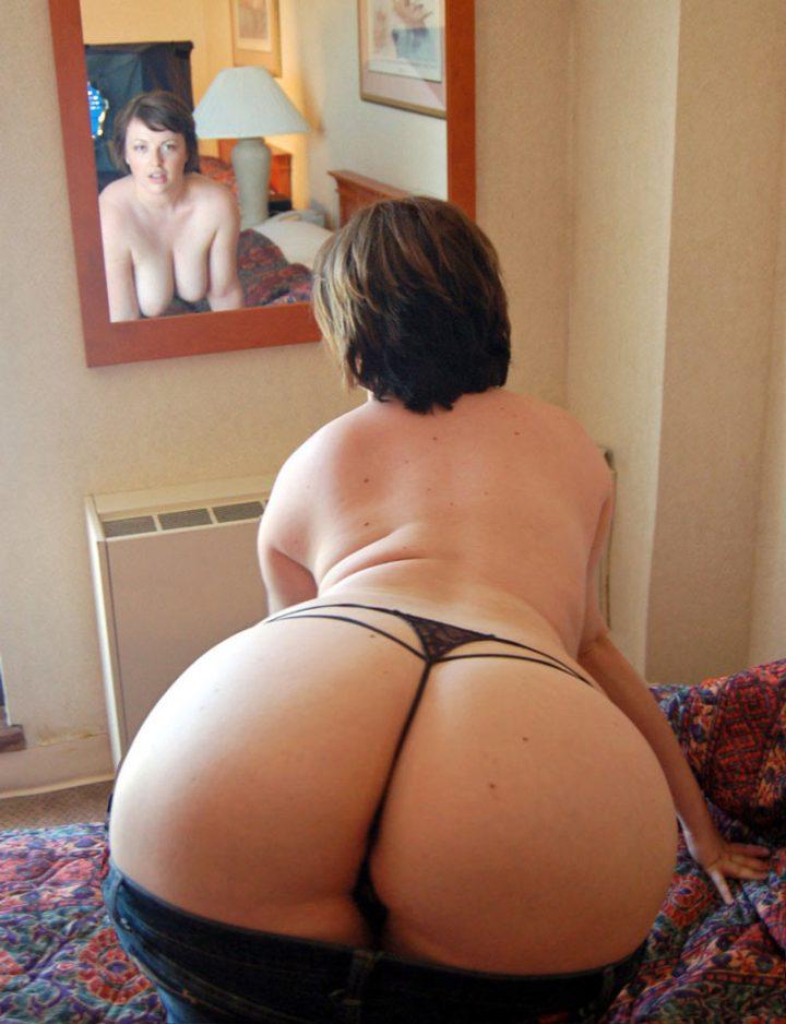 Раскрепощенная брюнетка стоит раком, отставив свою жопу и любуется в зеркало