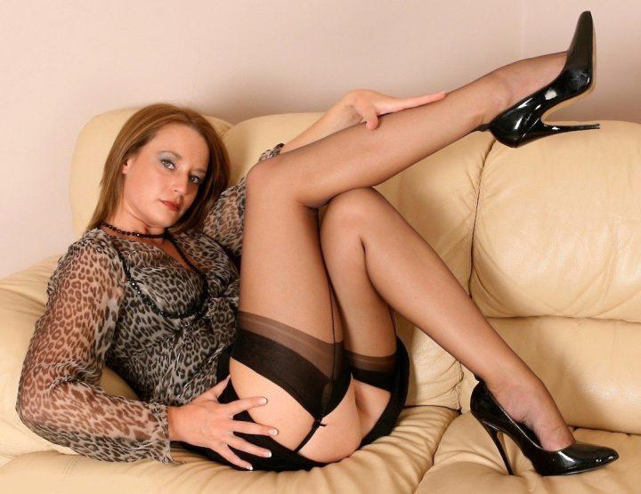 Стройная милфа лежит вна диване в чулках с поднятыми ногами