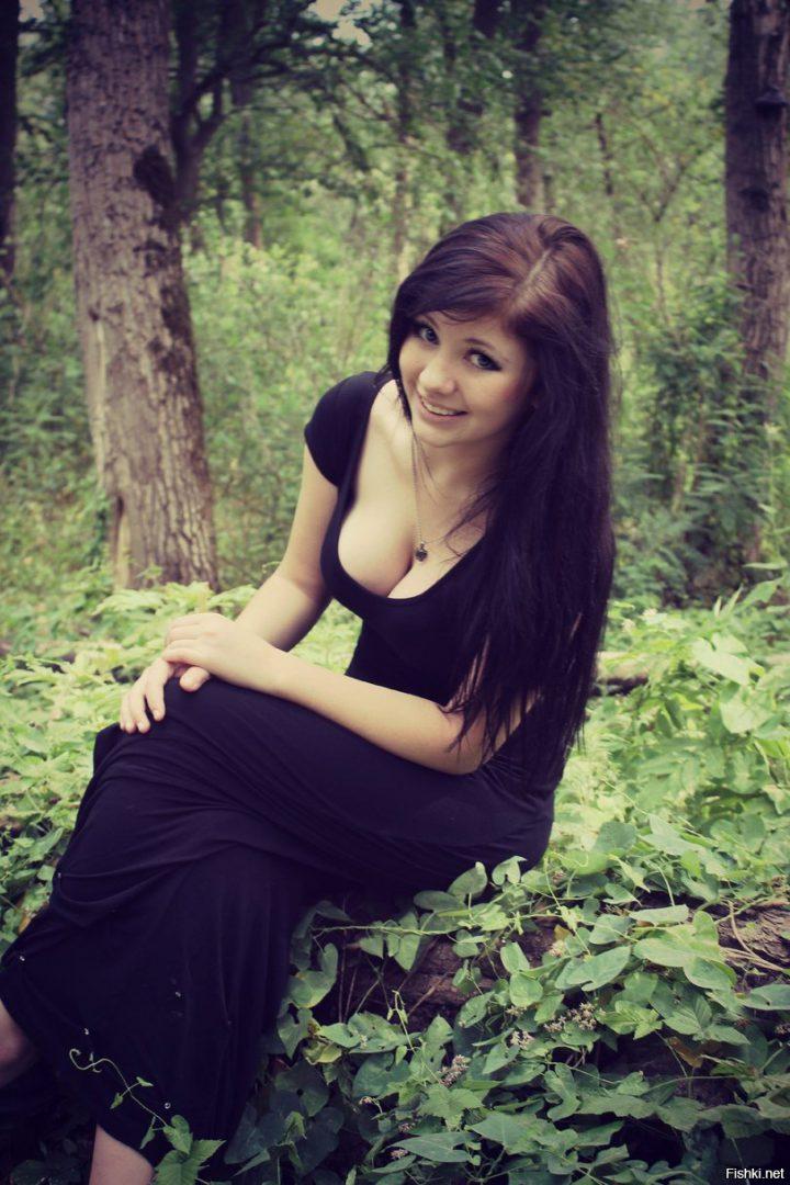 Девушка колдунья в черном длинном платье сидит на полянке.