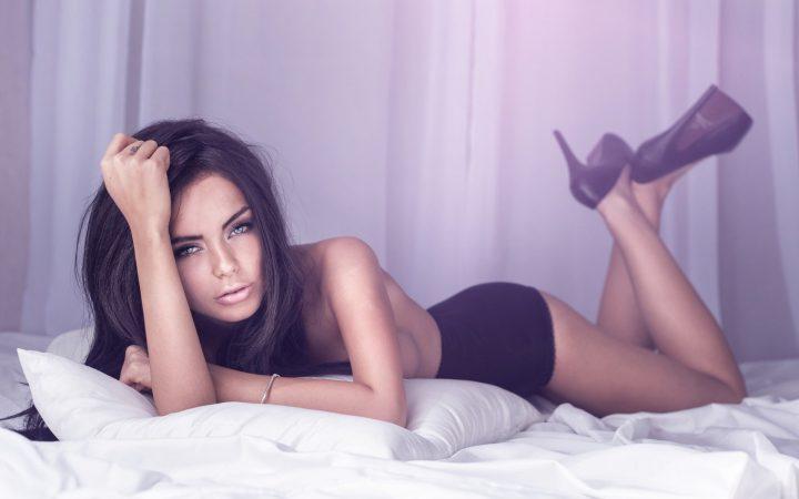 Обворожительная девушка в туфлях лежит на кровати.
