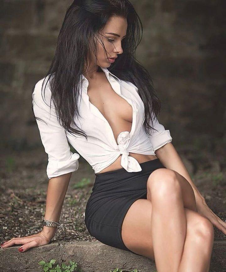 Красивая русская девушка сидит в юбке и в рубашке на голые сиськи.