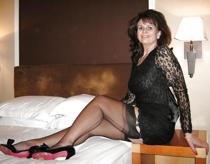 Раскрепощенная дама в очень коротком прозрачном платье в чулках со стрелкой сидит на столике у кровати.