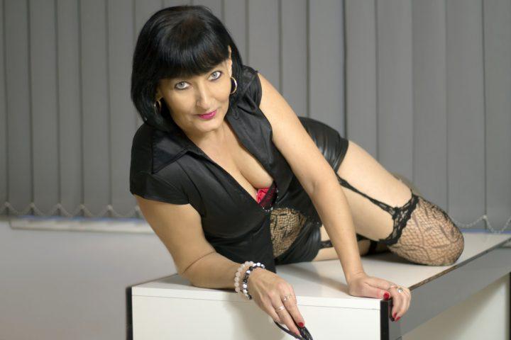 Роковая женщина в сексуальной позе лежит га столе.