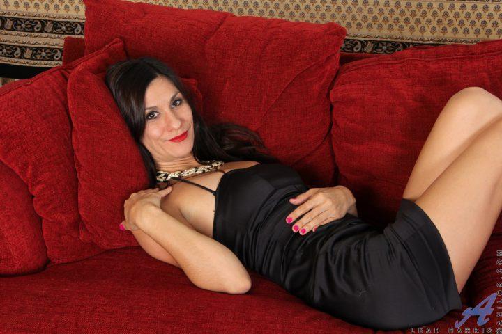Стройная женщина в облегающем черном платье сексуально лежит на бордовом диване.