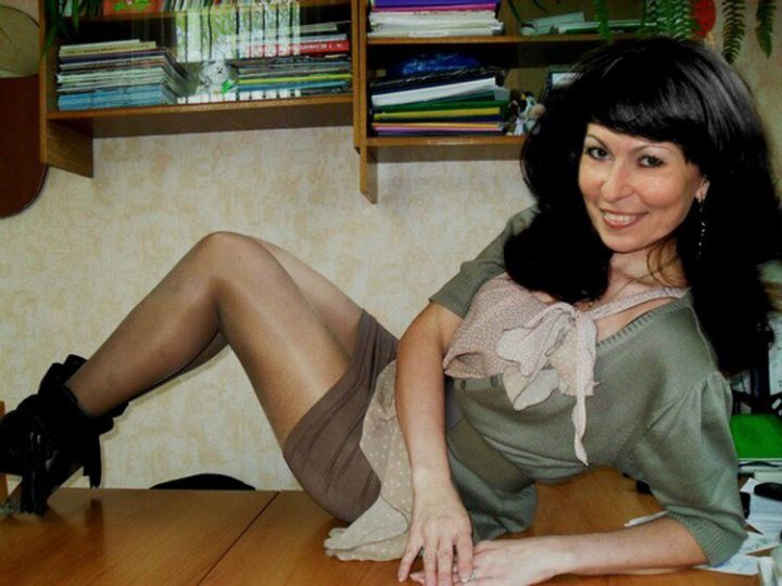 Смелая учительница сидит на столе показывая свои стройные ножки.