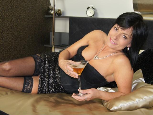 Милая женщина в корсете и в блестящей юбке с бокалом в руках лежит на кровати.