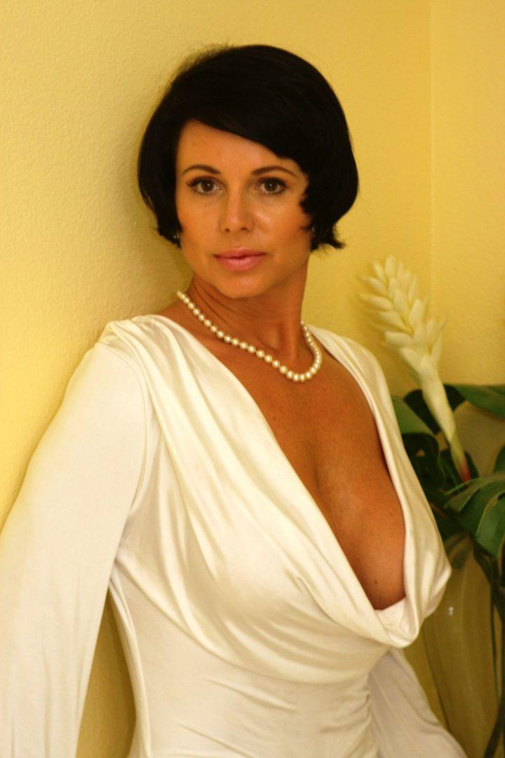 Приятная женщина с короткой стрижкой стоит у бежевой стены в белой блузке с глубоким декольте.