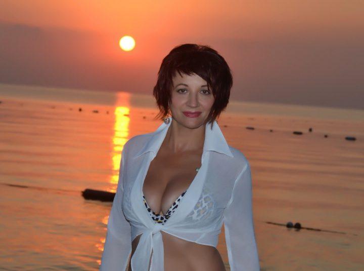 Смелая и открытая женщина стоит на закате в леопардовом купальнике.