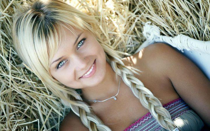 Русская девушка с косами и голубыми глазами лежит на сене.