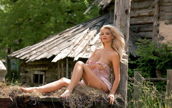 Блондинка модельной внешности сидит на сене в мини платье.