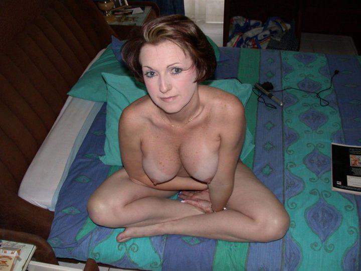 Милфа с прической и макияжем сидит на кровати в позе лотоса с голыми сиськами
