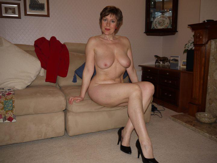 Зрелая милфа обнаженная в одних туфлях сидит на диване