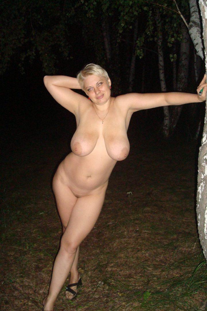Романтическая голая милфа с большими сиськами стоит в лесу