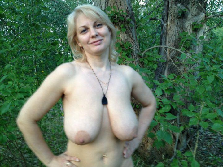Голая блондинка стоит в лесу с большими висячими сиськами