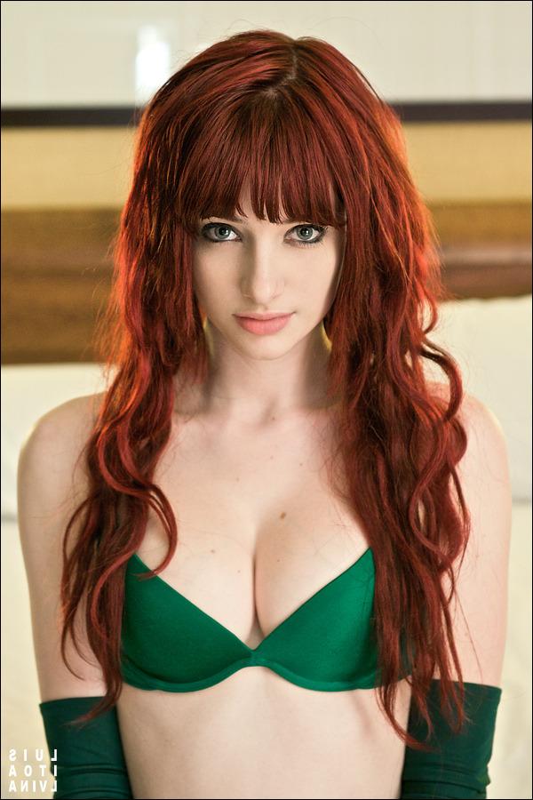 Яркая рыжая девушка с красивыми зелеными глазами.