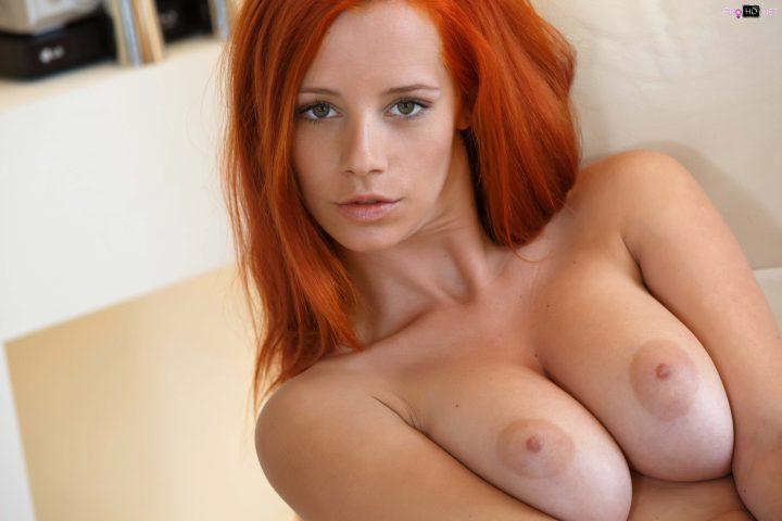 Напряженная девушка с рыжими волосами и большими сиськами.
