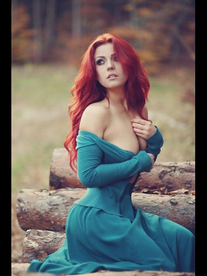Испуганная рыжая девушка полураздетая сидит в лесу.