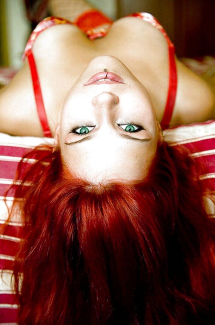 Девушка рыжая с магическими зелеными глазами и с сережкой в губе.