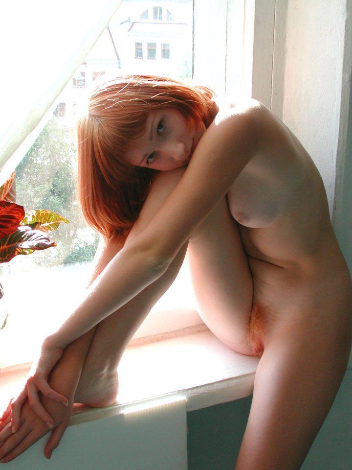 ГОлая девушка без комплексов с небритым лобком сидит на подоконнике.