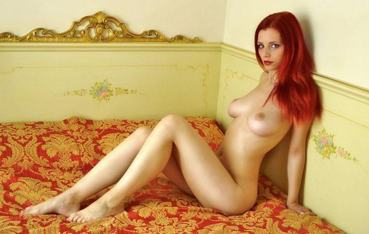 Красивая стройная девушка голышом сидит в кровати.