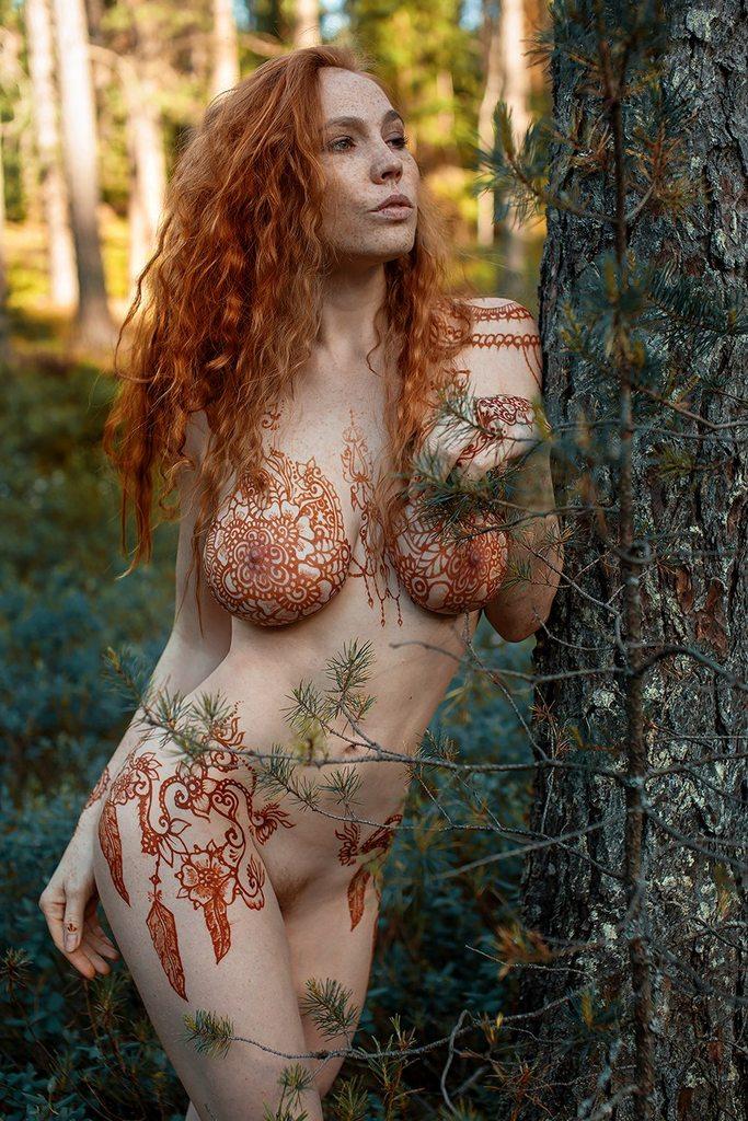 Голая девушка в веснушках вся разрисована хной.