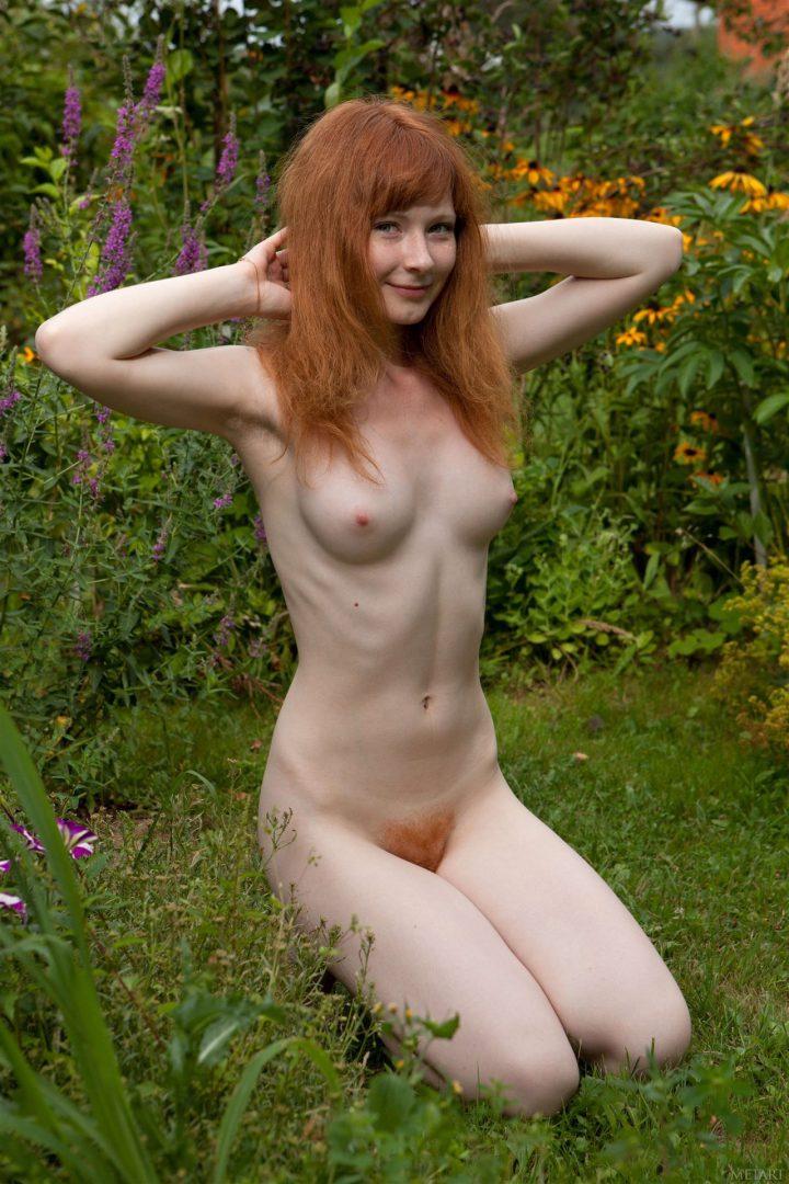 Молодая рыжая девушка обнаженная сиди т в саду, и на лобке тоже рыжие волосы.
