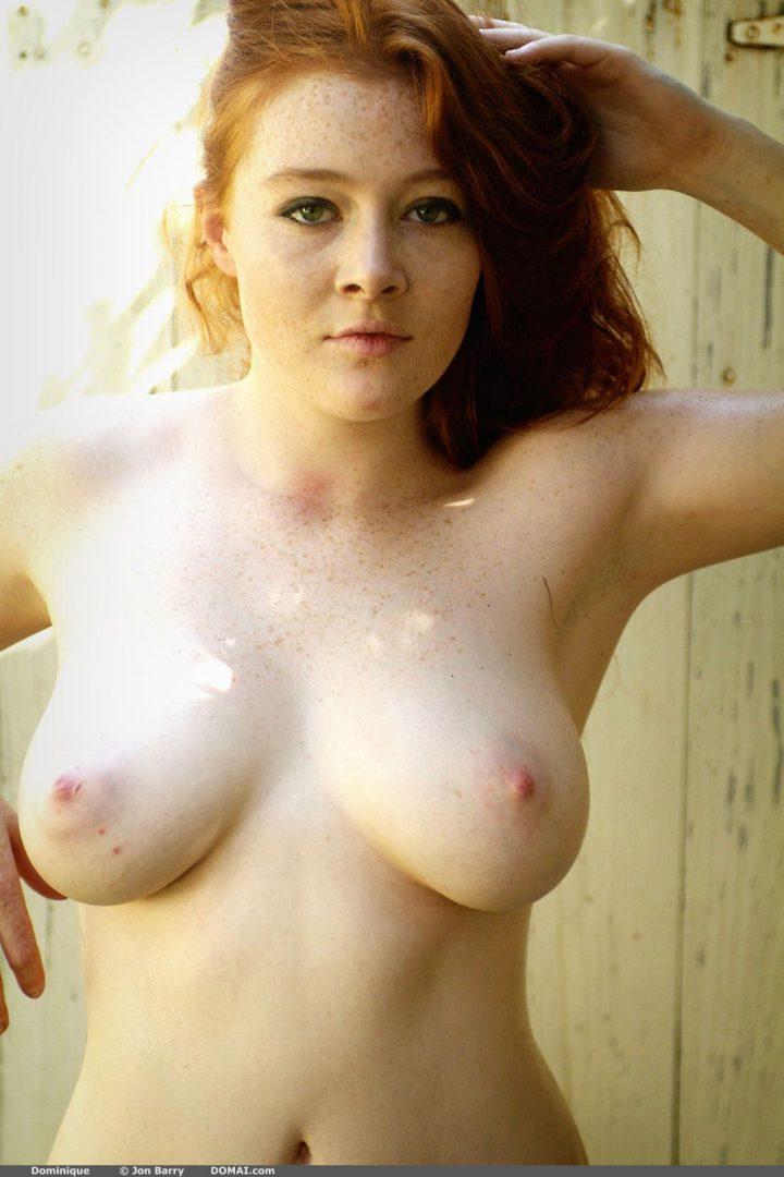 Милая девушка с веснушками на лице и на голой груди.