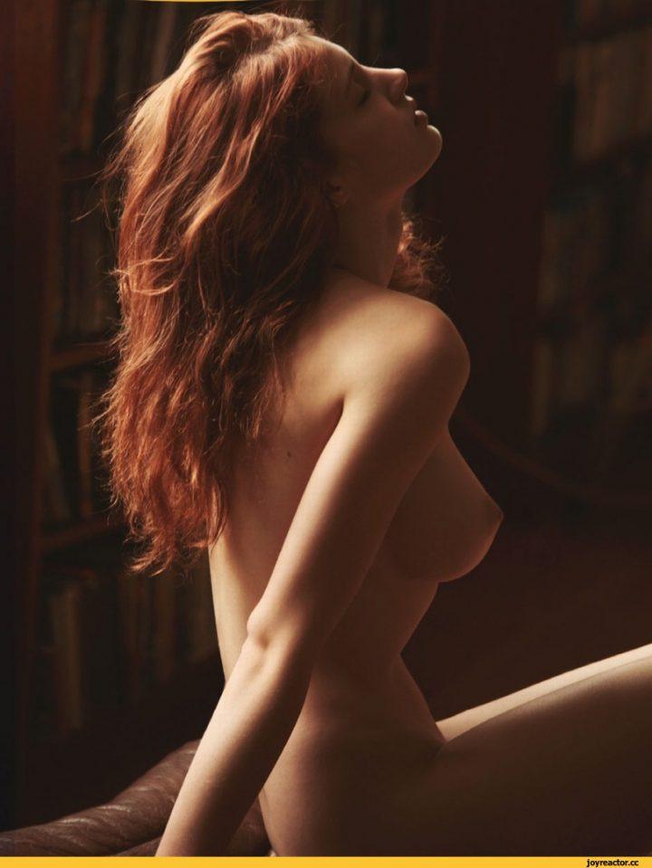 Рыжая девушка в темноте сидит в полуоборота.
