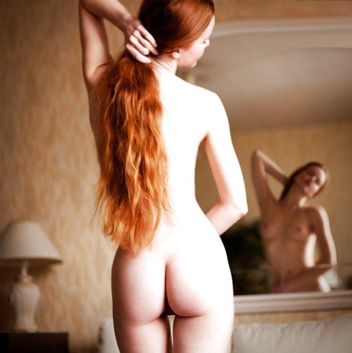 Голая рыжеволосая красотка стоит спиной и смотрит на себя в зеркало