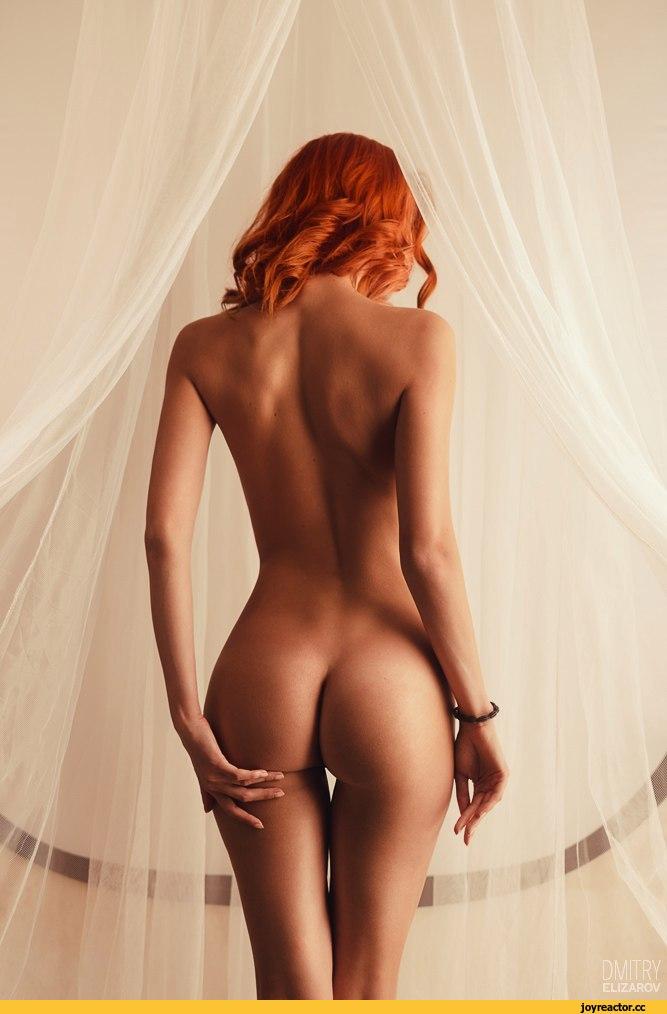 Девушка с рыжими волосами и красивым телом стоит спиной.