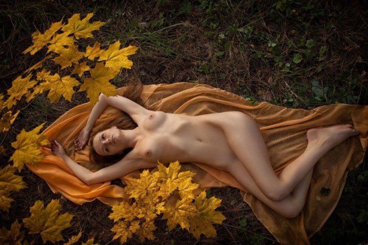 Красивая голая девушка лежит в осеннем лесу на рыжим покрывале.