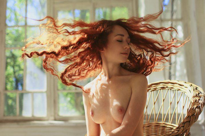 Нежная красотка с рыжими волосами сидит в плетеном кресле с голой грудью.
