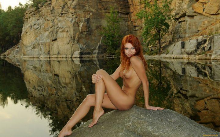 Голая рыжая русалка сидит обнаженная на камне.