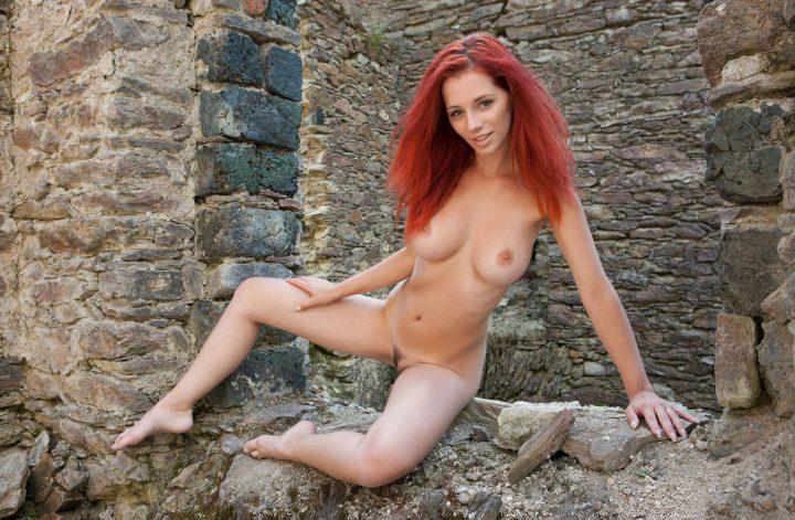 Смелая русская голая девушка сидит в развалинах.