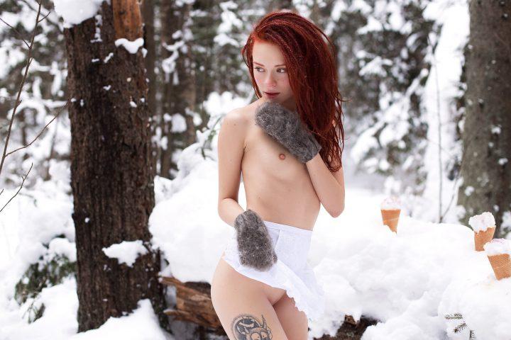 Закаленная девушка гуляет по зимнему лесу в варежках и одной юбочке.
