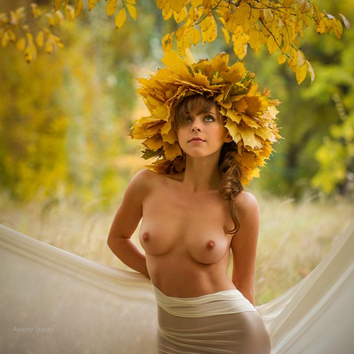 Рыжая красотка с осенним венком на голове обнаженная стоит в лесу.