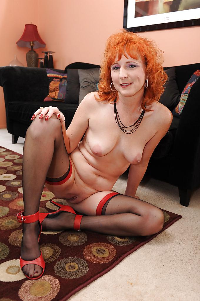 Рыжая развратная женщина сидит на полу широко расставив ноги.