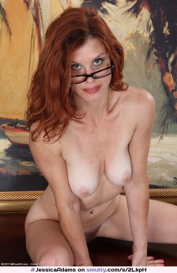 Женщина в очках с маленькими сиськами сидит на корточках.